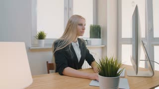 Upset woman sitting at workplace. Blond sad female in elegant clothes clutching head after failure or bad news sitting in light office at desk with computer.