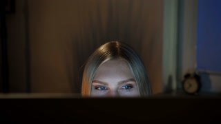 Woman peeking out computer monitor at night. Crop view of beautiful female sitting at night at computer and looking at camera over top of monitor with dark window on blurred background