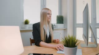 Woman showing thumbs down in office. Sitting at workplace young blond female in business suit looking at camera and doing thumbs down gesture of disapproval or dislike.