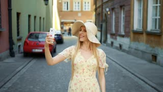 Woman taking selfie on street. Cheerful young woman walking on old European town street and taking selfie with smartphone.