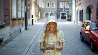 Woman texting on street. Cheerful woman in white hat walking on old town street and messaging with smartphone.
