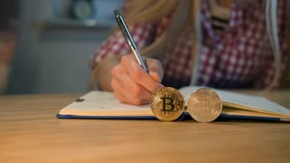 Woman writing in notebook with bitcoins nearby. Crop view of female hands in checkered shirt holding shiny metal pen and writing into daily planner with bitcoins placed on edges on foreground at night