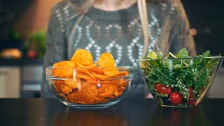 Young lady preferring crisp to salad. Attractive young woman choosing to eat healthy crisp for lunch while sitting at table in stylish kitchen and she eats these chips.