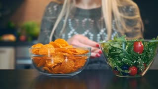 Young lady preferring salad to crisp. Beautiful young woman choosing to eat healthy crisp for supper while sitting at table in stylish kitchen and she eats these salad.