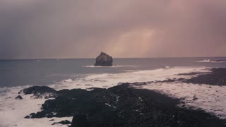 Adventurer in car stopped on the edge of ocean shore rocks t osee sunset in stormy weather Big cargo ships in sea behind and big waves Beautiful winter landscape.