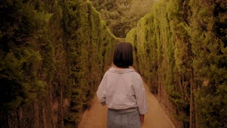 Attractive young girl walks in park labyrinth, turns away with smile and shakes her head showing that she does not know where to go Beautiful susnset time Handheld footage