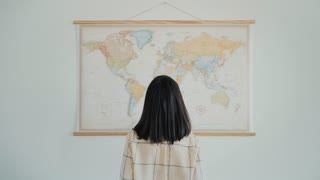 Back view on attractive brunette girl in glasses looks at big hanged world map isolated on white wall and points some directions as to plan travelling route
