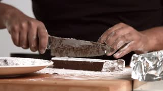 Black chief cuts freshly made chocolate brick to pieces and put it in sugar powder, close focus and camera moves slowly