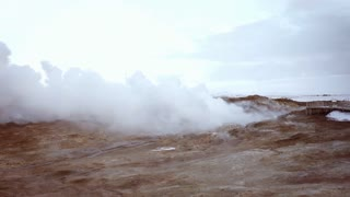 Chill view on the ground with geothermal paradox Volcanic terrain with smoke rises from underground in winter