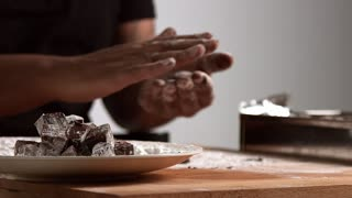 Close view professional artisan chief takes chocolate cubes from focused plate on front and makes candies and puts them in unfocused steel container behind