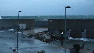 Dramatic slow motion of huge big waves smashing on concrete barrier wall that protects small empty port at strong heavy winter storm in ocean, early morning or evening low light time