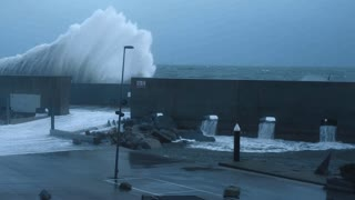 Dramatic slow motion of huge big waves smashing on concrete barrier wall that protects small marina at strong heavy winter storm in sea, early morning or evening low light time