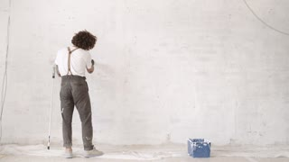 Funny curly man wears pants with suspenders carefully paints holes in brick wall with painting brush and white paint Home diy renovation