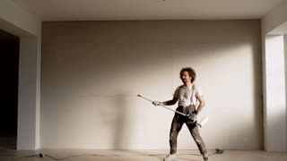 Funny curly man wears pants with suspenders imaginates and poses like he is playing punk hardcore music on electronic guitar from brush roller