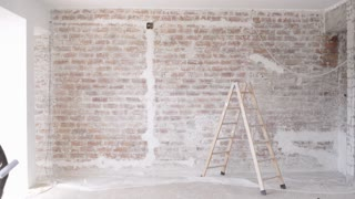 Funny curly man wears pants with suspenders starts to paint red brick wall with transparent oil paint and handy brush roller Home dyi renovation