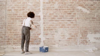 Funny curly man wears pants with suspenders starts to paint red brick wall with white paint and brush roller Home dyi renovation