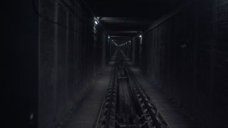 Pov view from underground train moving through dark horror narrow tunnel with cold dimmed laps on walls. Steel rope pulling mechanism seems on floor between rails. Looped video