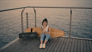 Pretty young brunette girl with tattoo on hand sits on wooden pier in front of longboard and small surf skate,looking at camera Wind sways her white t-shirt Beautiful sunset light Looped cinemagraph