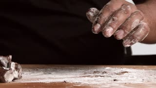 Slow motion closeup on wooden board, black chief hands put artisan chocolate piece on it and cut it to small square pieces