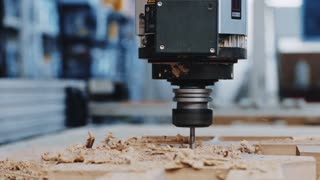 Slow motion front view of big drill head of industrial wood cut machines saws big piece of compressed laminate to cut out shaped mold. Saw dust dramatically flies out around. Artisan business concept