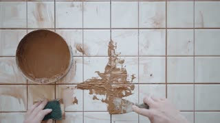Tattooed hands use palette knife and sponge to put and clean out accurately red cement adhesive on renovated ceramic tiles on kitchen table, top view