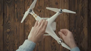 Top view, hands of aerial photographer remove dead exausted rechargeable lithium battery from white drone with rotors on rustic vintage wooden table. 10 February 2017 in Spain