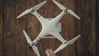 Top view, hands of male aerial videographer gently turn on small drone assembled and ready to fly. Copter initializes camera and blinks red and green led lamps, located on vintage wooden table