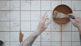 Top view, tattooed hands use palette knife to apply red tile adhesive from tin pot on white ceramic tiles on renovated kitchen table