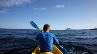 Action camera footage of athletic sporty man with healthy lifestyle choices paddles yellow kayak through open ocean waters with waves, stops to take breath, rest and drink refreshment from flask