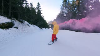 Action extreme sports camera shot of professional awesome snowboarder in bright colorful outfit ride, spin and do tricks on mountain slope, holds smoke bomb, concept freedom, winter activity
