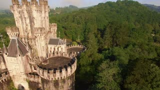 Aerial footage, drone flies by side of ancient fairy castle at sunny day and moves toward green fields and forests