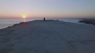 Aerial footage of drone fly over pier or concrete boardwalk at empty beach at sunset or sunrise, lonely figure of hipster man in sailor outfit, winter coat and sweater, concept adventures and explore