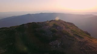 Aerial footage of epic and inspiring landscape of high alp mountains during sunset or twillight with beautiful sun light leaks and beams entering frame, mesmerizing and aweing nature