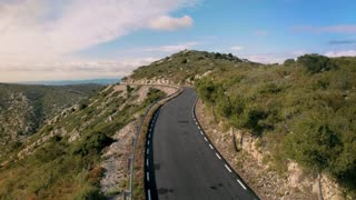 Amazing inspirational epic drone aerial footage of happy excited man riding skateboard in distance on empty scenic mountain road to success and independence