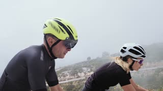 Beautiful blonde athlete woman struggles to climb on top of hill on her aero road bicycle on a windy day fighting the elements and her inner self. End of April 2017 in Spain