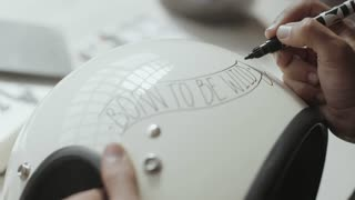 Calligraphy artists works on new art project, personalizing custom motorcycle helmet with hand lettering words, text says born to be wild, concept artisan, hand made, diy