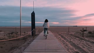 Camera follows girl on mint bicycle cycling at sunset time to sand beach next to sea shore, she stops at the end and dreamily looks forward