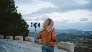 Camera follows hipster millennial young woman running up to road side on top of mountain summit, jumps on top of rocks, raises arms into air, happy and drunk on life, youth and happiness
