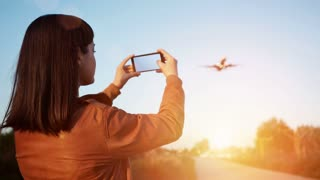 Cinemagraph loop Brunette girl in leather jacket takes video of big airplanes flying over her before landing in airport, on her smart phone at sunrise morning