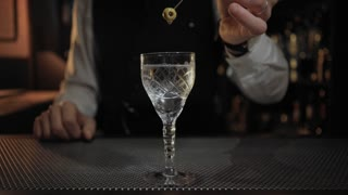 Cinemagraph of bartender holding up olive on sword stick over fancy and expensive alcoholic cocktail in vintage glass with dry martini dripping down from it