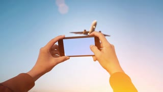 Cinemagraph of spotter girl hands holding smart phone and taking video of big airplanes flying over her head, isolated on clean blue sky background and with dramatic light leaks flares