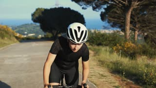 Close up portrait of strong cyclist woman rides mountain road on hard training puts out effort and power, to achieve sport goals. Happy and proud girl wears black special cyclist clothes and helmet