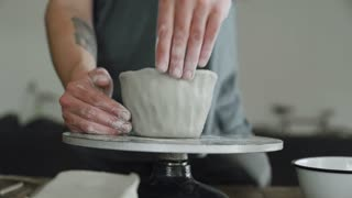 Close up view of artist's hands and fingers work on ceramic pot of raw grey clay on pottery wheel in his studio