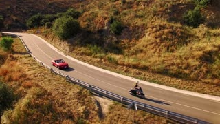 Epic aerial view from bird eyes on mountain serpentine road at sunny beautiful day, man in small red vintage convertible car chasing girl on retro motorbike at sunset summer day