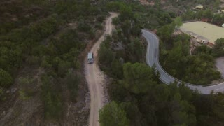 Epic and astonishing drone footage of small travel adventure van or caravan camper taking less ridden road through gravel and sand to explore unknown and find adventures