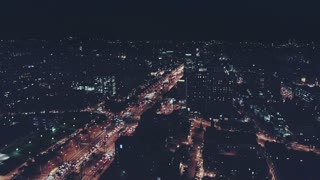 Epic and impressive aerial drone footage of midnight night time nocturne cityscape and city skyline flyover business centers offices and busy complex road and traffic jam