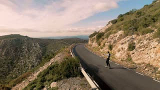 Epic conceptual shot of unrecognizable succesful businessman is skating with raised hands on curvy serpentine road in scenic montain landscape showing his happiness and escaping to freedom from his