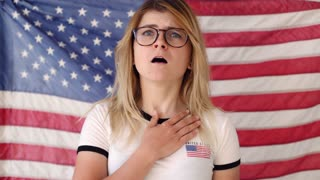 Funny looking excited blonde teenager in round glasses proudly declares anthem of united states of america in front of the flag in all the glory of fourth of july
