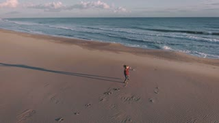 Happy and amazed teenager girl or young woman, runs towards sea or ocean on empty beautiful beach at sunset, excited to see water for first time, finally at vacation, free and full of energy
