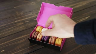 Male hand takes one tasty fresh macaron from gift box full of various cookies isolated on wooden table